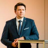 Georg Geczek steht vor einem Podest
