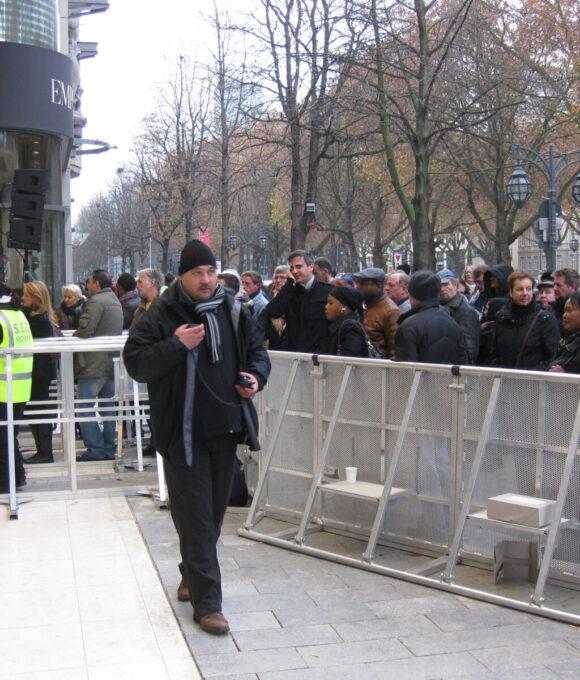 Sicherheitspersonal vor wartenden Personen vor einer Eingangsschleuse