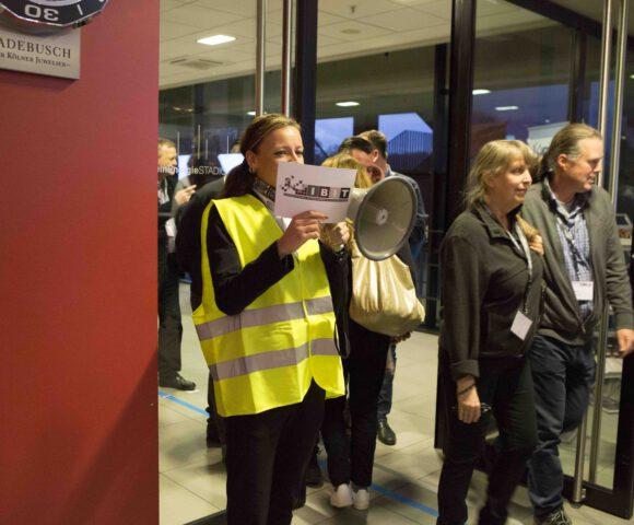 Eine Mitarbeiterin des Sicherheitsdienstes Special Security Services trägt ein Megaphon und eine Karte mit Anweisungen. Sie hilft bei einer Räumungsübung. Zwei Personen, ein Mann und eine Frau, verlassen das Gebäude im Rahmen der Räumungsübung durch eine Flügeltür.