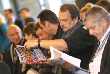 Besucher der IBIT Fachtagung lesen das IBIT Magazin