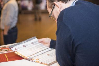 Ein Besucher der Fachtagung liest das IBIT Magazin