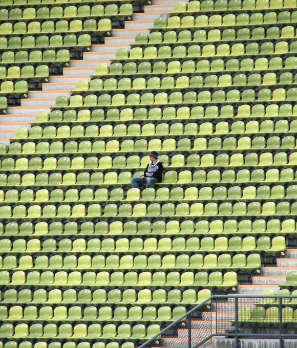 Leere Sitzplätze in Stadion. Mittig sitzt eine Person.